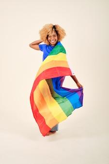 고립 된 배경에 서있는 동안 lgbt 프라이드 무지개 깃발을 들고 웃는 곱슬 머리 여자. lgbtq 커뮤니티와 자유 개념.
