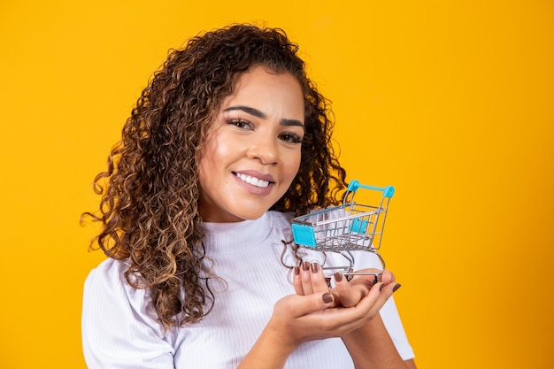 Smiling curly hair woman in shopping concept. young woman with a miniature cart. e-commerce and business. shopping car. woman shopper. yellow background.