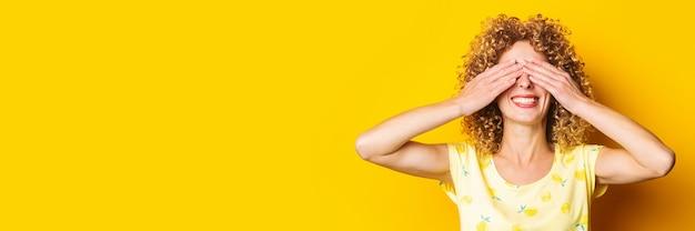 笑顔の縮れ毛の少女は、黄色の背景に彼女の手のひらで目を覆った
