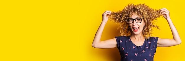 Улыбающаяся кудрявая молодая женщина в очках держит в руках прядь волос на желтом фоне