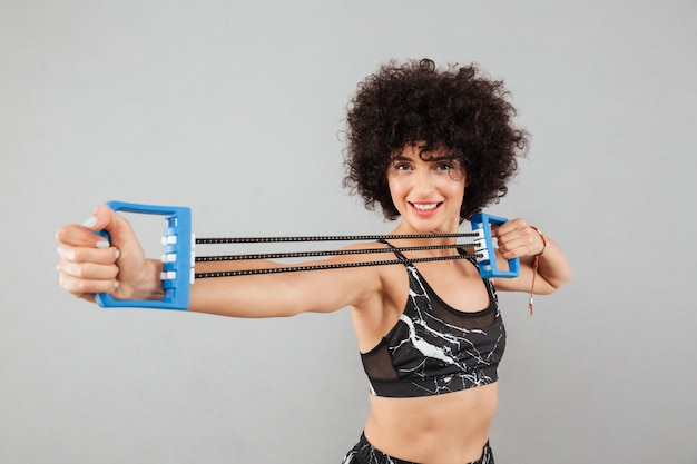 Smiling curly sports woman doing exercise with hand expander