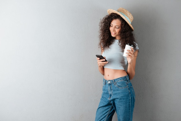Smiling curly woman drinking coffee and using smartphone over gray background