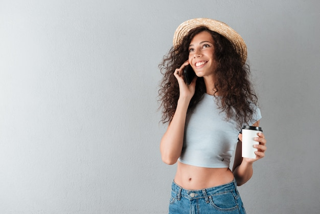 Smiling curly woman in hat drinking coffee and talking by the smartphone