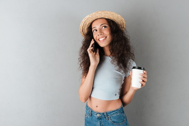 Smiling curly woman in hat talking by the smartphone with coffee in hand and looking up over gray background