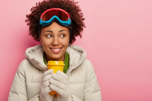 La donna riccia sorridente tiene il caffè da asporto, si riscalda con una bevanda calda, indossa un cappotto invernale bianco e occhiali da sci