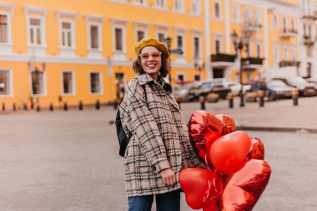 오렌지 안경에 웃는 곱슬 여자는 아름다운 건물의 벽에 정면으로 보인다