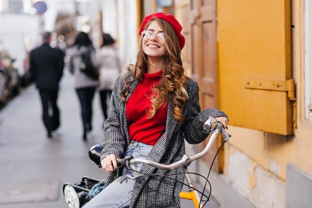 Donna riccia sorridente in maglione rosso che guida sulla bicicletta intorno alla città in una giornata fredda