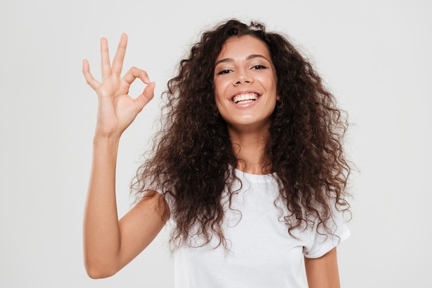 Smiling curly woman showing ok sign