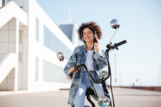 Smiling curly woman sitting on modern motorbike outdoors and listening music