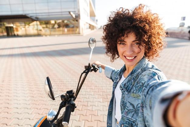Улыбающаяся кудрявая женщина сидит на современном мотобайке на свежем воздухе и делает селфи