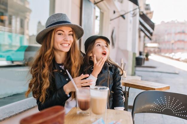 Sorridente donna riccia in cappello vintage e giacca di pelle in posa con la figlia eccitata nella caffetteria, mentre beve il caffè.