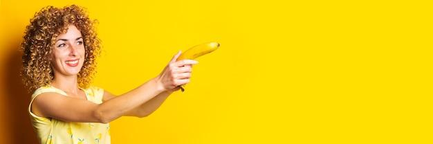 노란색 바탕에 바나나 권총을 들고 곱슬 젊은 여자를 웃 고.