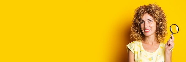 노란색 표면에 돋보기와 웃는 곱슬 젊은 여자