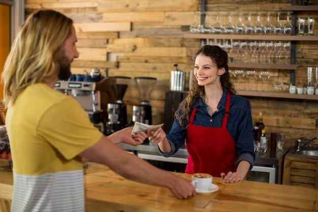 Smiling customer paying bill by cash at counter