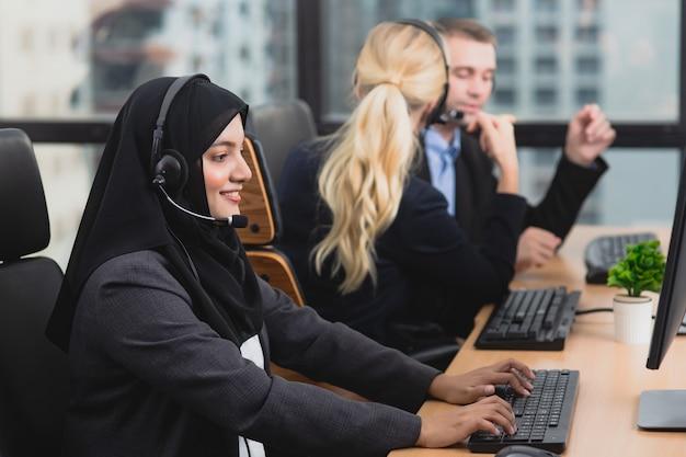 Усмехаясь команда дела оператора работы с клиентом в шлемофонах работая в офисе. азиатская мусульманская девушка