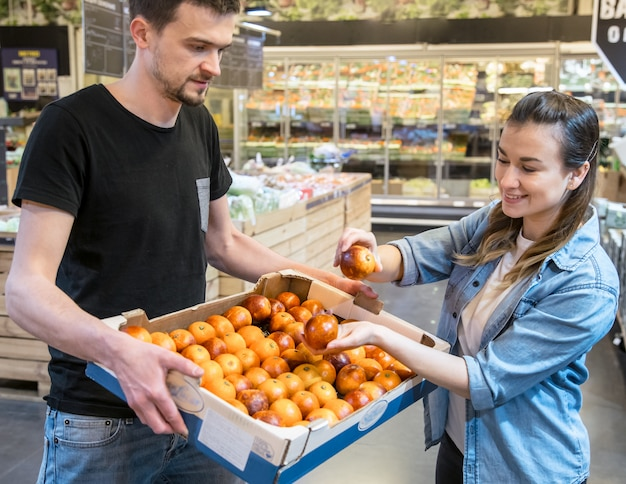 Smiling customers buying sicilian oranges in grocery section