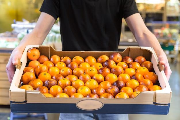 Улыбающиеся клиенты покупают сицилийские апельсины в продуктовом отделе