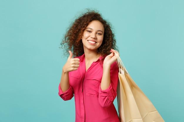 웃고 있는 귀여운 아프리카 소녀가 파란색 청록색 벽 배경에서 쇼핑한 후 구매한 패키지 가방을 들고 엄지손가락을 치켜들고 있습니다. 사람들은 진심 어린 감정 라이프 스타일 개념입니다. 복사 공간을 비웃습니다.