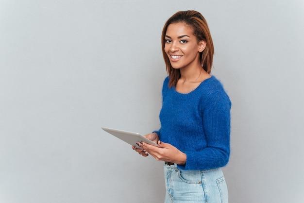 手にタブレットコンピューターと横に立っているセーターでかわいいアフリカの女性の笑顔