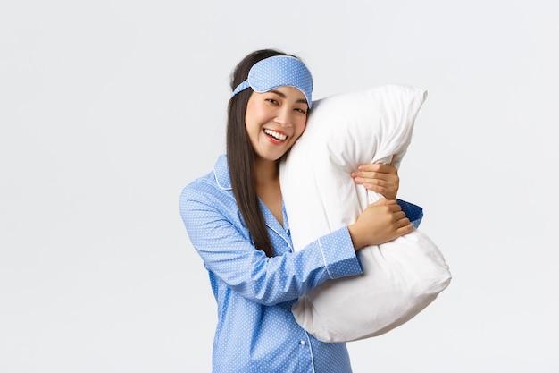 Улыбающаяся милая азиатская девушка в спальной маске и пижаме обнимает подушку, как спит, чувствует себя довольной, когда ложится спать, чувствует себя комфортно и довольна на белом фоне