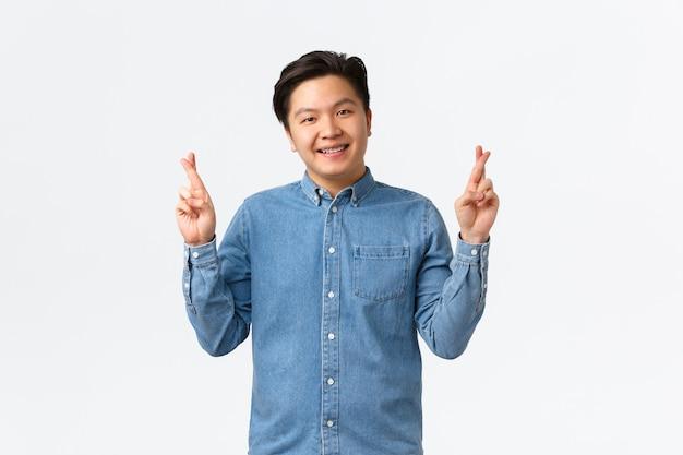 Sorridente simpatico uomo asiatico che ha fede, crede che i sogni si avverino, incrocia le dita buona fortuna, prega o esprime desideri, fortunato su sfondo bianco, anticipando risultati positivi.