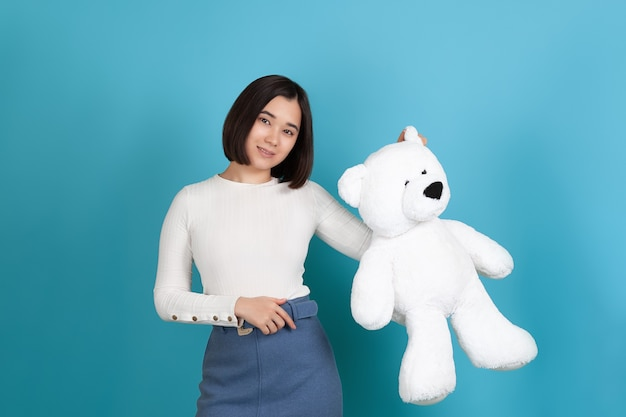 Smiling, cute asian woman in casual clothes holding a large white teddy bear by the ear