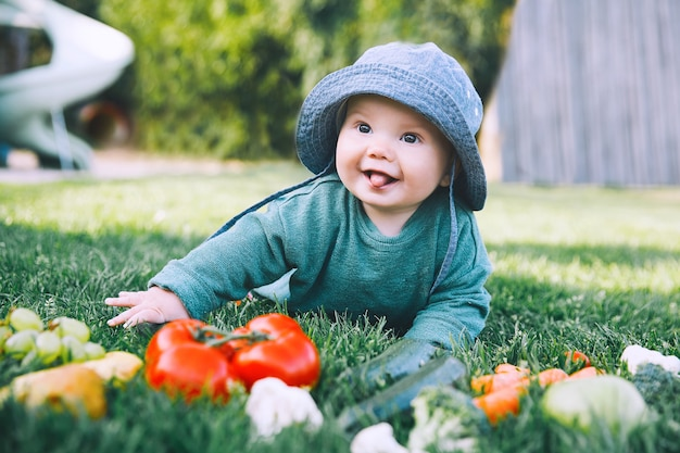 Smiling cute baby and different fresh fruits and vegetables on green grass