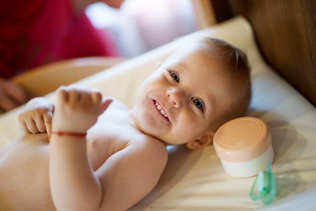 Улыбающийся милый малыш лежал на плохом с соской и кремом возле головы