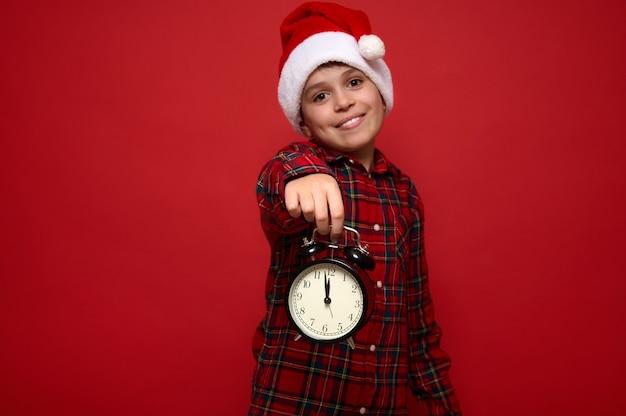 Улыбающийся милый мальчик в шляпе санты и красной клетчатой рубашке держит в вытянутых руках черный будильник с полуночью на циферблате и показывает его на камеру. рождество и новый год концепция для рекламы