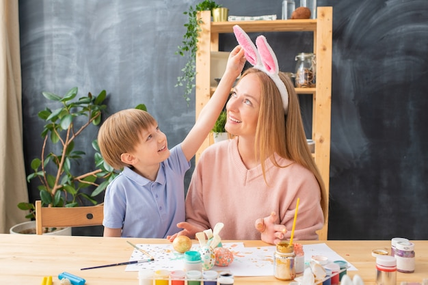 Smiling cute boy touching rabbit ears headband on mothers head while they painting eggs in kitchen