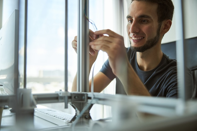 인쇄를 시작하기 전에 3d 프린터를 조정하는 t- 셔츠에 귀여운 백인 남성 학생 미소