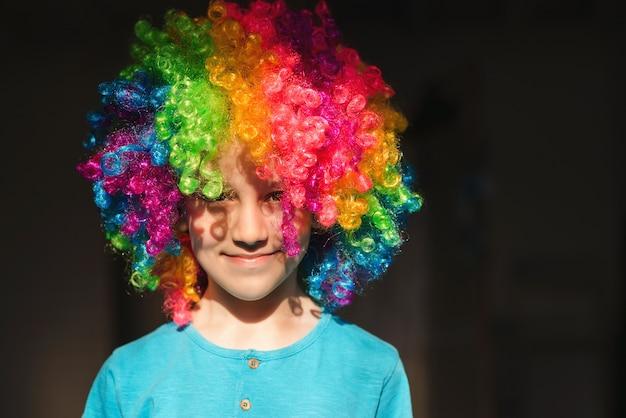 광대 가발에 웃는 귀여운 아이. 생일 키즈 파티. 집에서 놀고 있는 재미있는 꼬마 광대. 1월 1일 만우절 컨셉입니다. 행복한 어린 시절