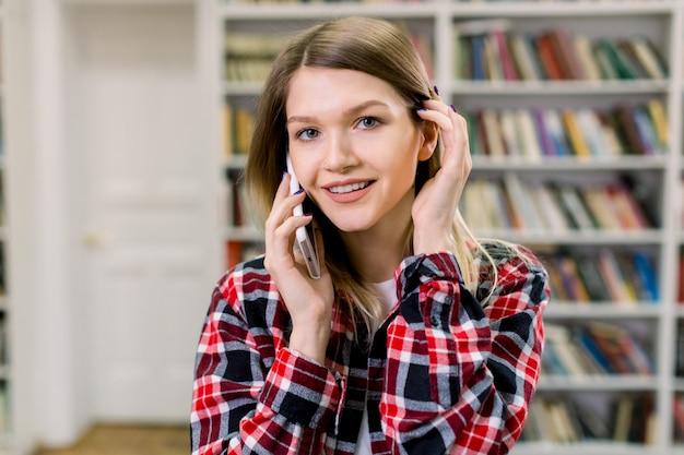 Улыбающаяся милая уверенная 25-летняя девушка в повседневной клетчатой рубашке, разговаривает по телефону, позирует на камеру на полках пространства