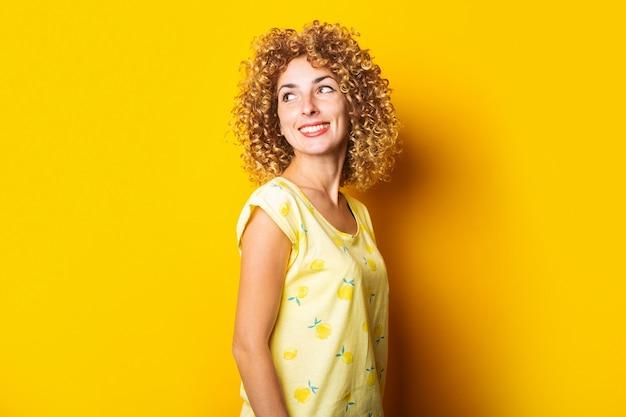 笑顔のかわいい縮れ毛の女の子は黄色の背景を振り返る