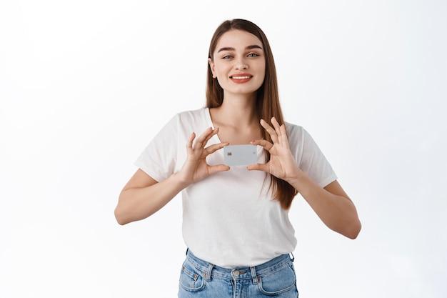 Улыбающаяся милая девушка-клиент банка, держащая кредитную карту обеими руками возле груди, выглядящая довольной и счастливой, предлагает новую банковскую функцию, рекомендуя банковские услуги, стоя над белой стеной