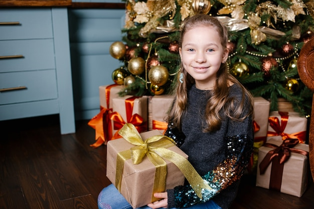Улыбаясь милая девочка, держа в руке рождественский подарок у елки.
