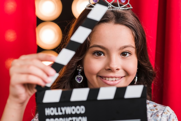 Smiling cute girl holding clapperboard