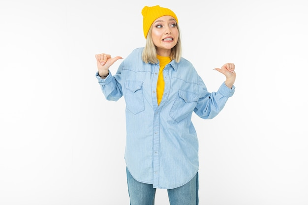 スタイリッシュなデニムシャツと黄色い帽子の笑顔のかわいい女の子は、白いスタジオの背景のように表示されます。