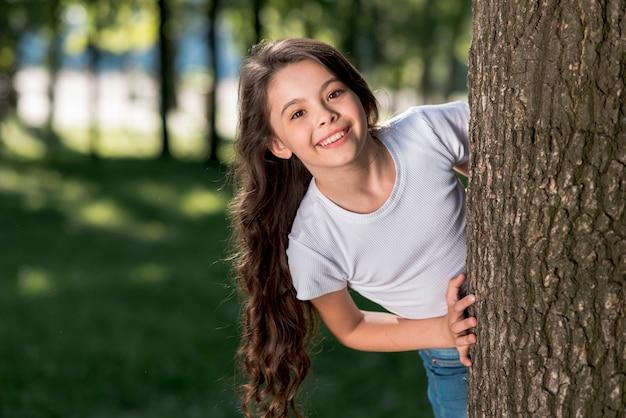 야외에서 나무 줄기 뒤에서 바라 보는 웃는 귀여운 소녀
