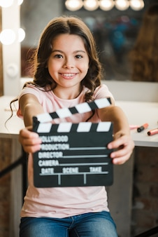 Smiling cute girl showing clapper board