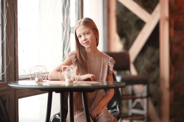아늑한 카페에서 테이블에 앉아 웃는 귀여운 소녀