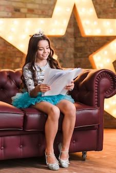 Smiling cute girl sitting on sofa reading scripts at backstage