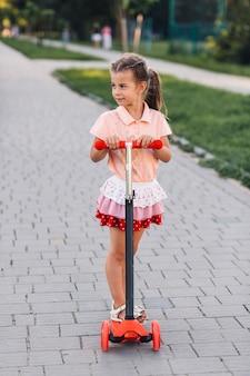 공원에서 킥 스쿠터에 서있는 귀여운 소녀 미소