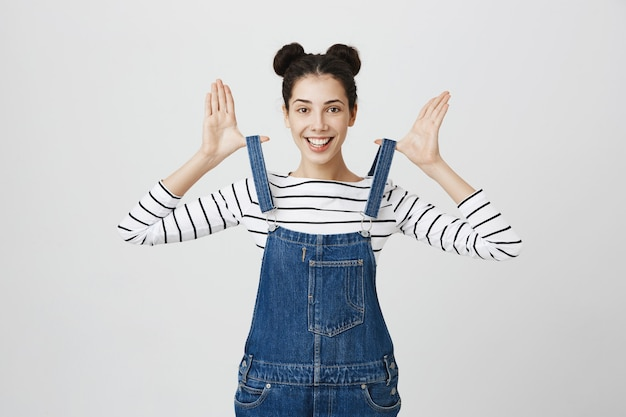 Smiling cute girl stretching overalls straps and smiling