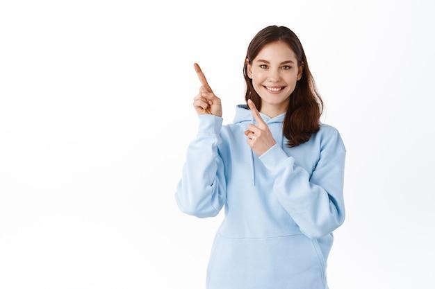 웃고 있는 귀여운 여학생이 왼쪽 상단 모서리에 손가락을 옆으로 가리키며 광고를 보여주며 후드티를 입고 흰 벽에 서 있습니다.