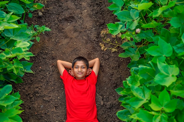 Улыбающийся милый индийский мальчик, лежащий на земле