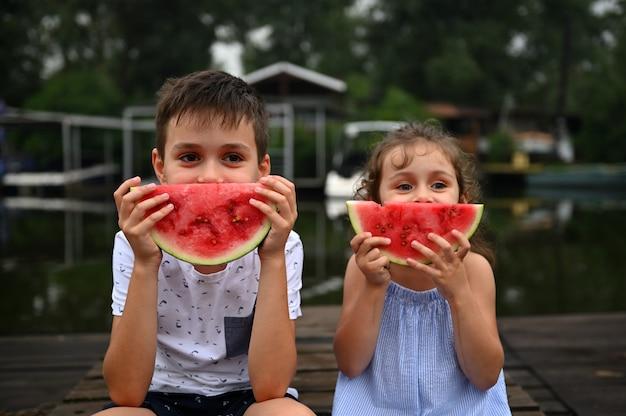 スライスしたスイカで口を覆い、桟橋に座って、夕方に田舎の夏休みを楽しんでいるかわいい子供たちの笑顔。愛らしい男の子と女の子の顔に幸せな幼稚な感情