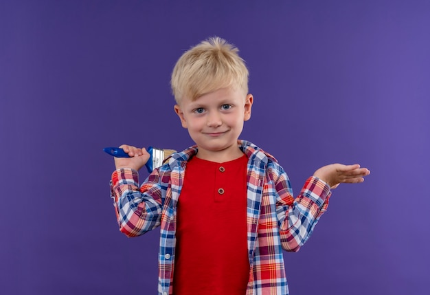 A smiling cute little boy with blonde hair wearing checked shirt holding paint brush looking on a purple wall