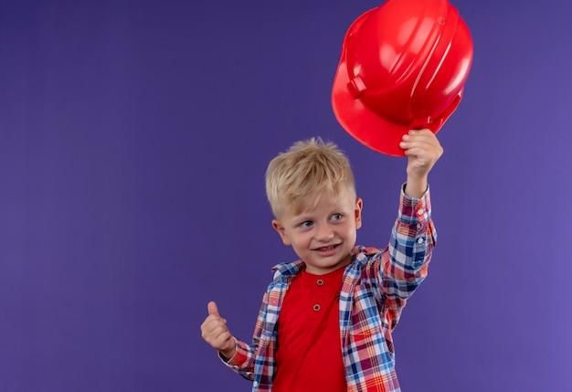 Un ragazzino sveglio sorridente con capelli biondi che indossa l'elmetto rosso di decollo controllato mentre osserva il lato su una parete viola