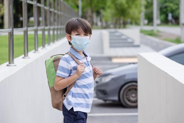 학교 배낭과 보호용 안면 마스크를 들고 학교 첫날을 위해 준비된 웃고 있는 귀여운 소년